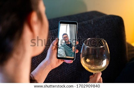 Woman Calling By Video Chat Her Friend And Drinking Wine With Him. Online Date, Meeting With Friend. Stay Home. Social Distance and Isolation Royalty-Free Stock Photo #1702909840