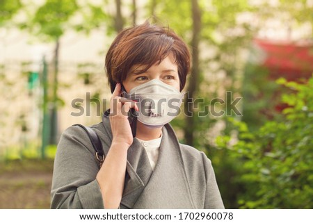 Mature woman in medical mask phone outdoors #1702960078
