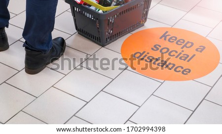 the inscription on the floor of the supermarket: keep a social distance. Selective focus #1702994398
