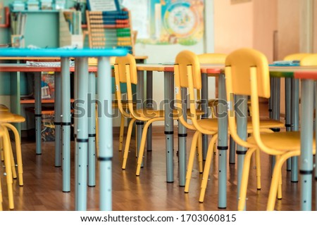 Living room: Chairs, table and toys. Interior of kindergarten. Soft selective focus. Royalty-Free Stock Photo #1703060815
