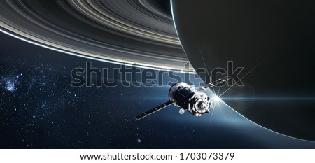 Spaceship on orbit of the Saturn planet. Exploration of the space. Rings of the planet. Sci-fi wallaper. Elements of this image furnished by NASA