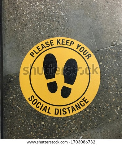 Sign on the floor of a public space requesting that people maintain social distance