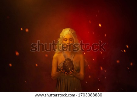 Art photo Portrait young beautiful woman blond hair in fire ash stained face. Fantasy power queen holding in hands egg mystic dragon. Backdrop mixed neon light red fiery sparks smoke. Halloween Image