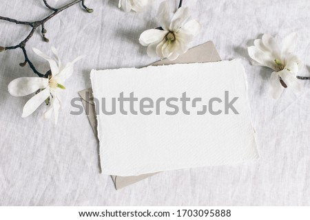 Wedding stationery mock-up scene. Blank horizontal greeting card, envelope on linen tablecloth background with white magnolia stellata tree branches and ribbon. Feminine still life. Flat lay, top view