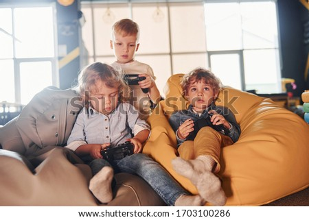 Kids in casual clothes sitting together with controller and playing video games. #1703100286