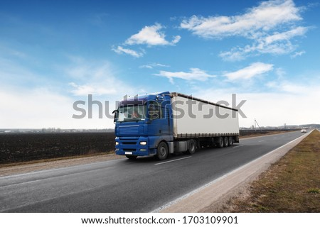 A big blue truck and a white trailer with space for text on the countryside road against a blue sky with clouds #1703109901
