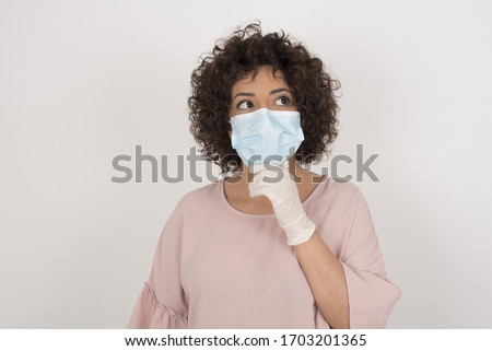 Shot of contemplative thoughtful Young woman keeps hand under chin, looks thoughtfully upwards, dressed in casual clothes. wearing face mask protection against infectious disease. #1703201365