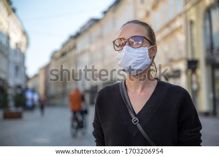 COVID-19 pandemic coronavirus. Young girl in city street wearing face mask protective for spreading of coronavirus disease 2020. Close up of young woman with medical mask on face against SARS-CoV-2. #1703206954