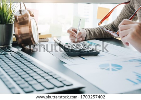 Close up of businesswoman or accountant hand holding pen working on calculator to calculate business data, accountancy document and laptop computer at office, business concept #1703257402