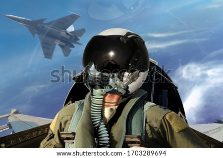 Fighter pilots cockpit view under cloudy blue sky Royalty-Free Stock Photo #1703289694