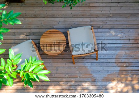 Top view of two stylish wooden chairs with cushions and a small wooden table at a balcony of a room in a resort, surrounded by garden  #1703305480