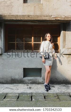 Portrait of beautiful young asian woman posing near building