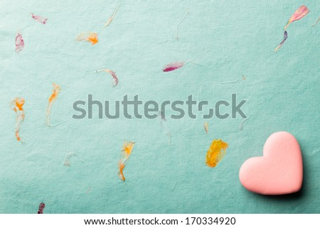 Pink heart-shaped candy on a paper background. #170334920