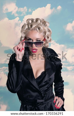 beautiful young woman  on sky background in old fashion clothes representing pinup and retro style winks. Girl dressed in a black cloak with red lipstick and sunglasses.