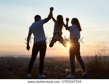 Silhouette of father mother and their daughter spending fun day outside the city on the hill on the sunset with a beautiful city view, dad and mom holding girl by hands and she is hanging, back view #1703367334