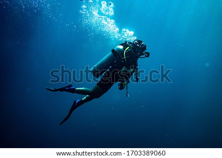 Scuba diving safety stop performed in the deep blue sea Royalty-Free Stock Photo #1703389060