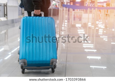 Traveler Tourists dragging luggage, Baggage reclaimed Cancel flights stop, prevent COVID-19 virus disease, stop Covid-19 travel suitcase in empty airport that restrict to avoid world pandemic COVID-19 #1703393866
