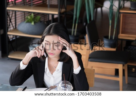 An Asian businesswoman is sitting down on the phone in a restaurant seriously. #1703403508