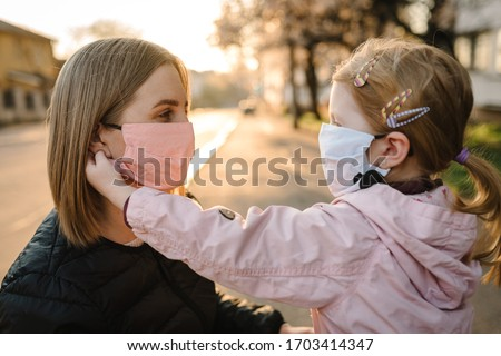 Coronavirus the end concept. No more covid-19. Little girl, mother wear masks walk on street. Mom removes mask happy child. Family with kid outdoors. celebrating success. Pandemic is over, has ended. #1703414347