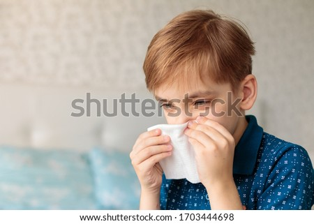Young boy  with allergy sneezing and blowing his nose in a handkerchief. House background #1703444698