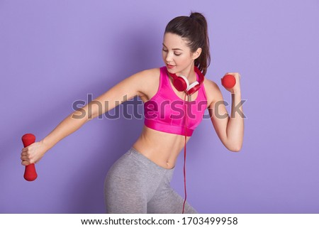 Picture of sporty good looking cute fitness trainer doing physical exercises, holding red dumbbells, having headphones around neck, wearing pink top and grey leggins. People and sport concept.