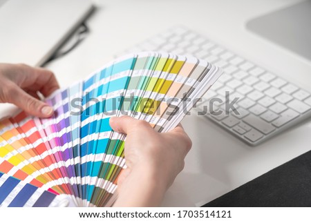 Graphic designer chooses colors from palette guide for painting and printing a new creative business work