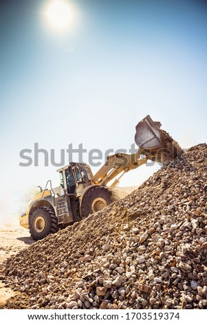 A heavy duty digger crawls to the top of the rubble pile scooping building debris into a heap.  Dust hovers around.  The sun is shining through the dust. Royalty-Free Stock Photo #1703519374