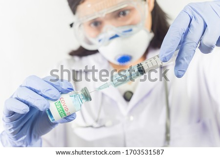Female doctor in a protective face mask with a stethoscope on shoulder holding syringe and COVID-19 vaccine. Healthcare And Medical concept. #1703531587