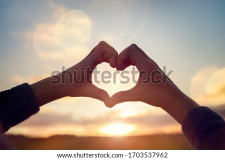 Heart shape with childs hands over sunset sky background