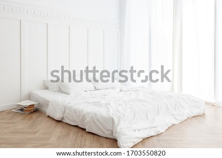 Interior view of white unmade messy bed on a wooden floor in the morning with transparent curtain and sunlight #1703550820