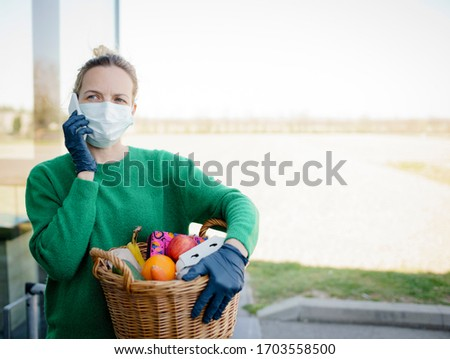 Pretty woman with face mask and green pullover and black gloves makes a phone call after shopping and is holding her shopping basket #1703558500