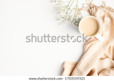 Flat lay plaid and cup of coffee on white desk. Hygge, autumn cozy mood, comfort concept. Flat lay, top view Royalty-Free Stock Photo #1703559325