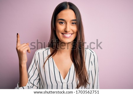 Young beautiful brunette woman wearing casual striped shirt over isolated pink background pointing finger up with successful idea. Exited and happy. Number one.