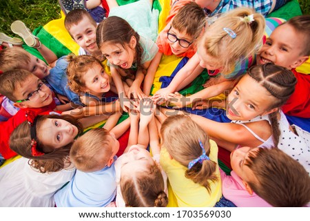 Top view kids in circle laying on colorful cloth Royalty-Free Stock Photo #1703569030