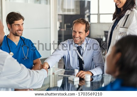 Businessman shaking hands with doctor in meeting room. Doctor and representative pharmaceutical shaking hands in medical office. Salesman with new medicines shaking hands in hospital with medical team #1703569210
