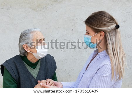 Portrait of friendly caregiver posing with elderly ill woman wearing surgical mask because of covid-19 pandemic Royalty-Free Stock Photo #1703610439