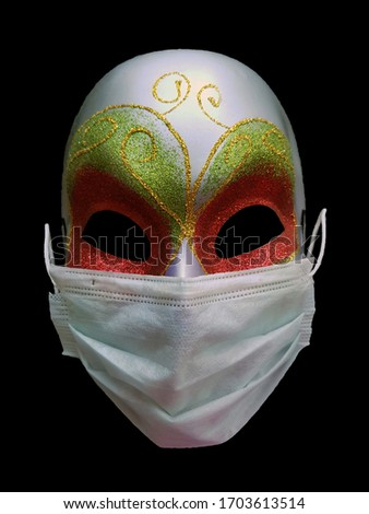 Conceptual photo of a carnival venetian mask in a protective medical mask reflecting the possible psychological and mental state of a person during a coronavirus pandemic isolated on black background
