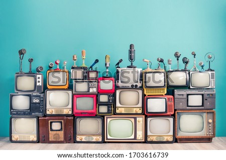 Retro TV receivers set from circa 60s, 70s and 80s of XX century, old classic microphones for press conference front mint blue wall background. Broadcasting, news concept. Vintage style filtered photo Royalty-Free Stock Photo #1703616739