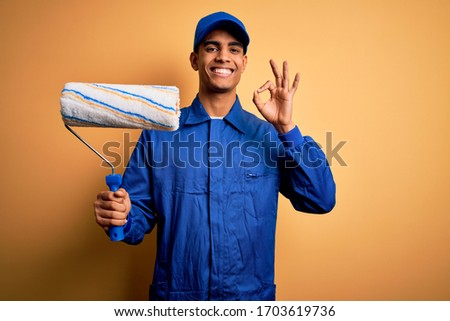 Young handsome african american painter man wearing uniform using painting roller doing ok sign with fingers, excellent symbol