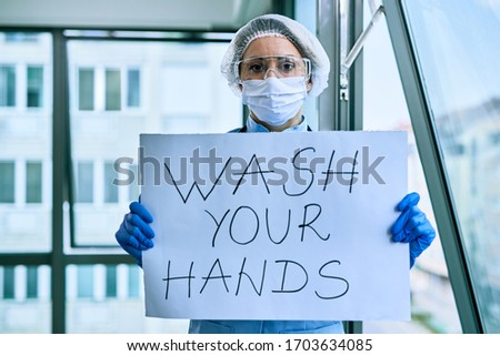 Female doctor holding placard with wash your hands text as appeal during coronavirus pandemic.  #1703634085