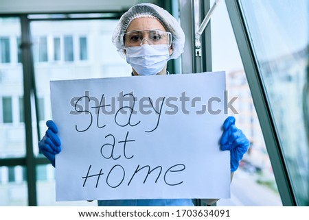 Female doctor holding placard with stay at home text as appeal during COVID-19 epidemic.  #1703634091