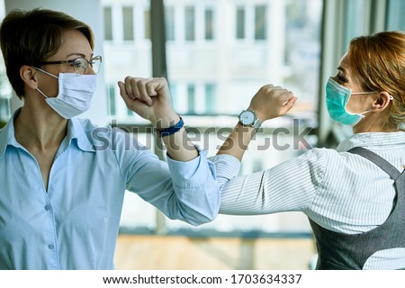 Two businesswomen elbow bumping while greeting each other in the office during COVID-19 epidemic.  #1703634337