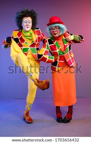 Two clowns a man and a woman with makeup in bright colored costumes are fooling around and showing a presentation using various accessories. April Fools Day concept. Birthday for kids