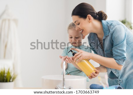 A cute little girl and her mother are washing their hands. Protection against infections and viruses.    #1703663749