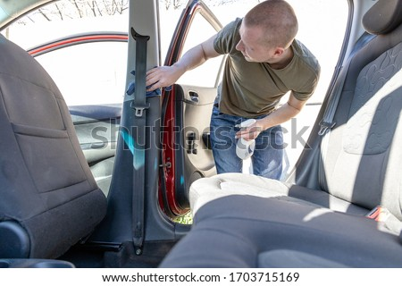 young man washes a door in a car on a sunny day #1703715169