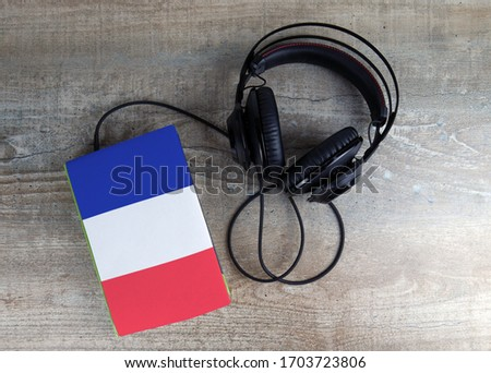 Headphones and book. The book has a cover in the form of France flag. Concept audiobooks. Learning languages. #1703723806