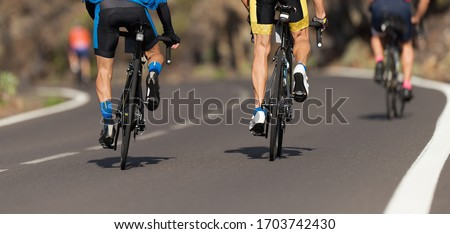 Cycling competition cyclist athletes riding a race at high speed, detail on gear wheels and feet Royalty-Free Stock Photo #1703742430