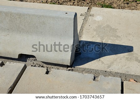 Concrete block separating the panel road from the pavement. road made of panels with concrete divider. Jersey barrier, Jersey wall, modular concrete barrier employed to separate lanes of traffic. #1703743657