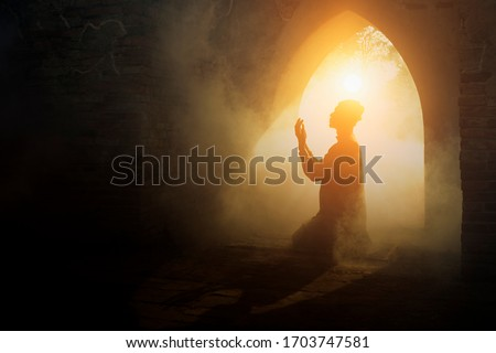 Silhouette of muslim man having worship and praying for fasting and Eid of Islam culture in old mosque with lighting and smoke background                                   Royalty-Free Stock Photo #1703747581