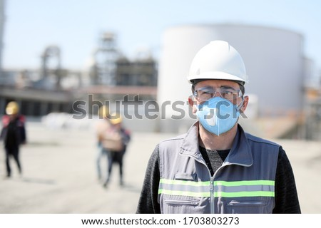 The worker (staff, engineer) protects himself from covid-19 (coronavirus) with a protective mask in the construction site. #1703803273